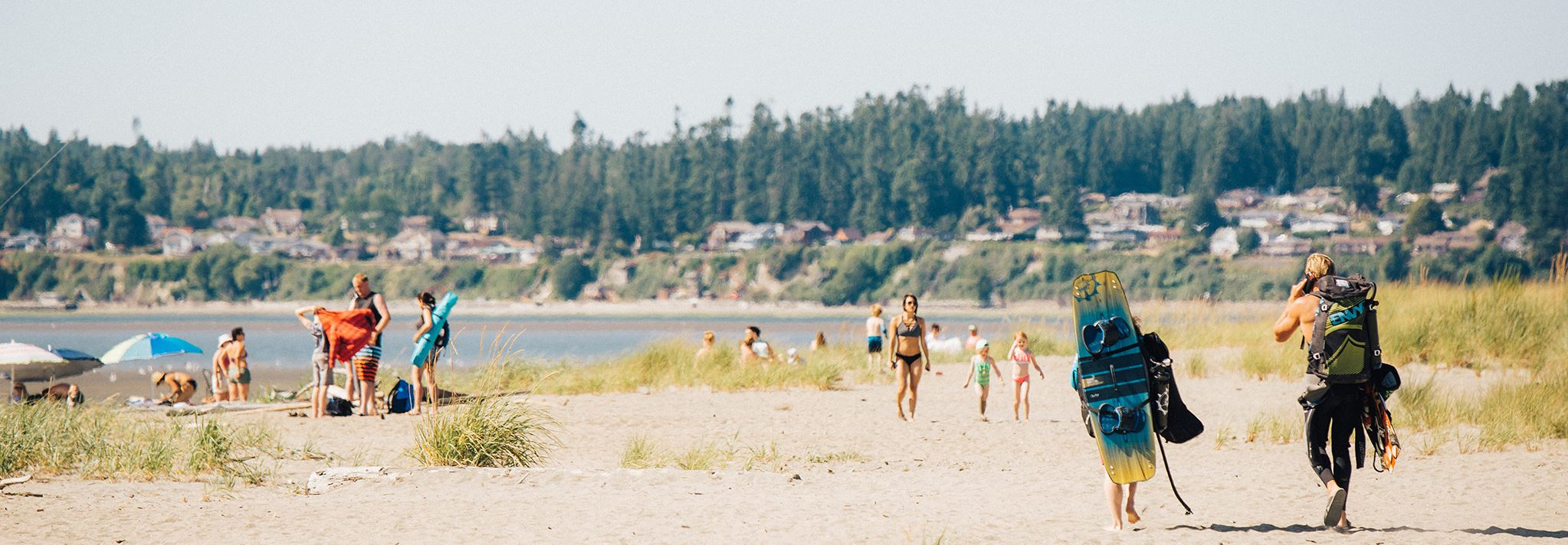 Two people with kiteboards, a mother with two kids, and a family walk on Jetty Island's beach.